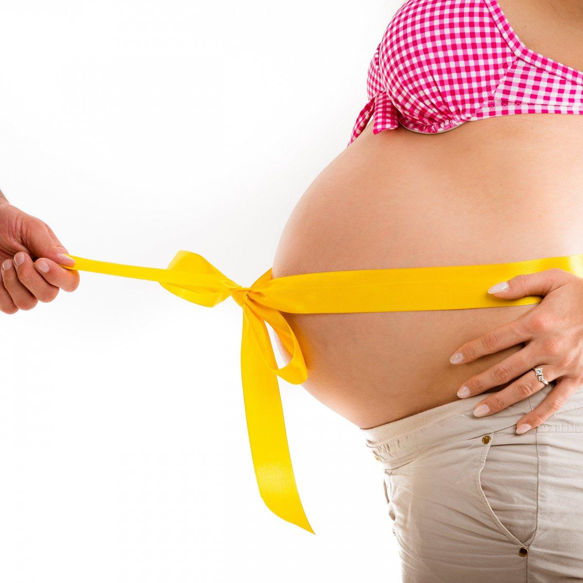 Ein Geschenkband, welches um den schwangeren Bauch gebunden ist. Der Partner packt es dann aus.