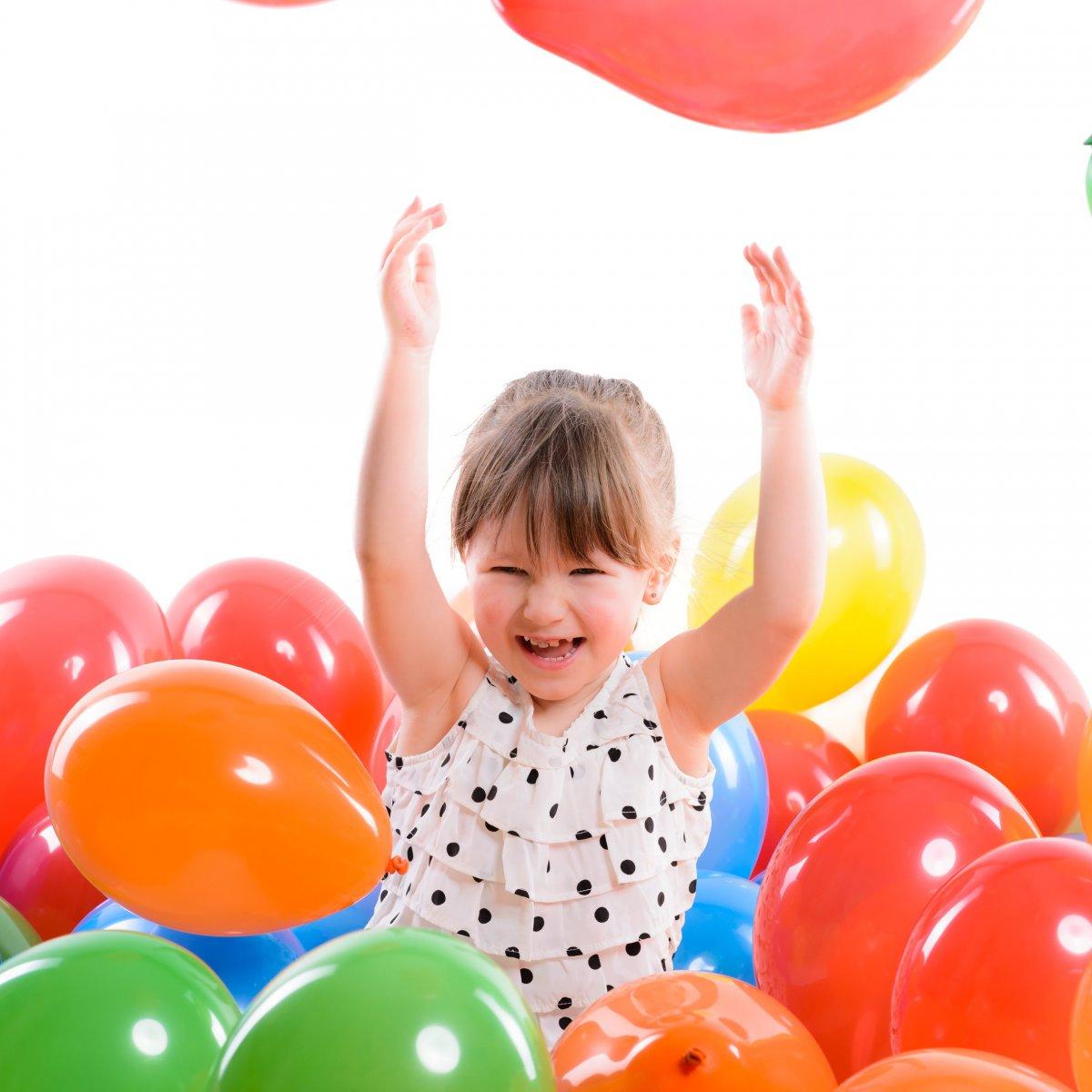 Ein Mädchen sitzt in einem Meer aus bunten Luftballons