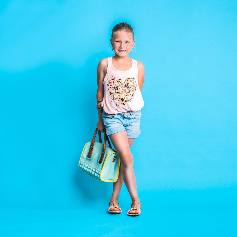 Ein Mädchen als Model mit einer türkisen Handtasche